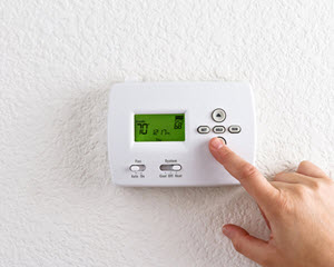 image of homeowner with programmable thermostat in Woodbridge New Jersey